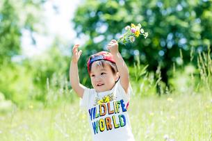 公園で野花を持つ男の子の素材 [FYI01075273]