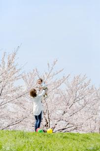 桜の咲く土手で息子を抱き上げる母の素材 [FYI01075283]