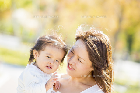 秋の公園で母親に抱かれる女の子の素材 [FYI01075377]