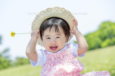 公園で笑いながら花を持つ女の子の素材 [FYI01075406]