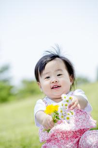 公園で笑いながら花を持つ女の子の素材 [FYI01075415]
