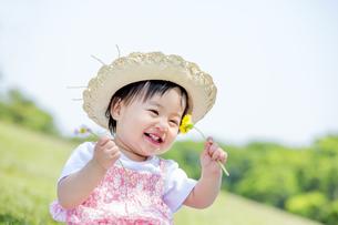 公園で笑いながら花を見る女の子の素材 [FYI01075432]