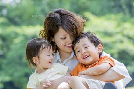 公園で子供たちを抱きかかえる母親の素材 [FYI01075444]
