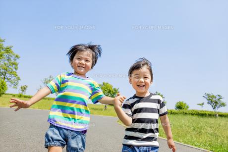 公園を手をつないで走る男の子たちの素材 [FYI01075448]