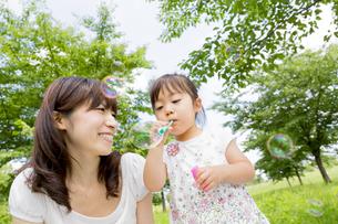 公園でシャボン玉を吹く娘と母親の素材 [FYI01075449]