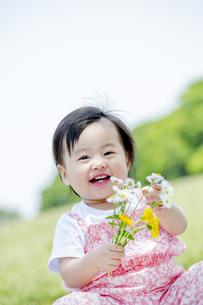 公園で笑いながら花を持つ女の子の素材 [FYI01075455]