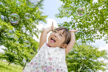 公園でシャボン玉を追う女の子の素材 [FYI01075463]