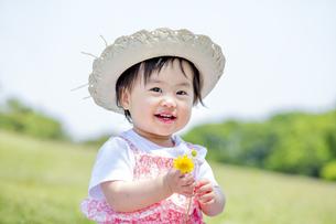 公園で笑いながら花を持つ女の子の素材 [FYI01075469]