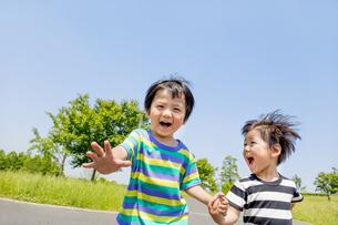 公園を手をつないで走る男の子たちの素材 [FYI01075470]