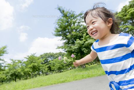 公園を花を持って走る女の子の素材 [FYI01075471]