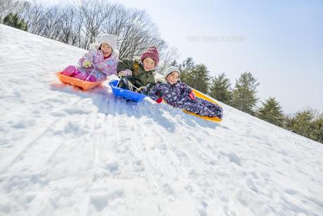 雪の公園でソリ遊びをする子供たちの素材 [FYI01075473]