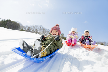 雪の公園でソリ遊びをする子供たちの素材 [FYI01075477]