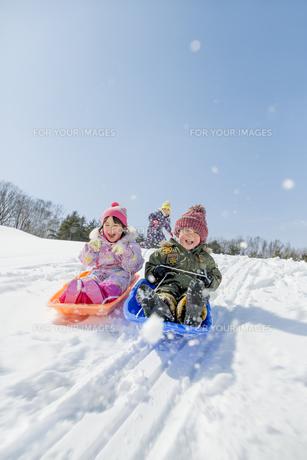 雪の公園でソリ遊びをする子供たちの素材 [FYI01075485]