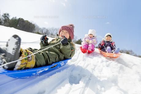 雪の公園でソリ遊びをする子供たちの素材 [FYI01075487]