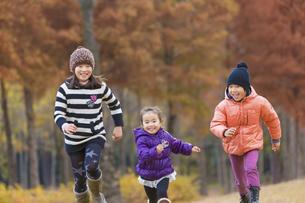 秋の公園を走る3人兄弟の素材 [FYI01075493]