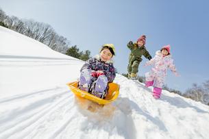 雪の公園でソリ遊びをする子供たちの素材 [FYI01075494]