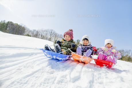 雪の公園でソリ遊びをする子供たちの素材 [FYI01075496]