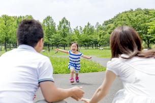 公園で両親に向かって走る娘の素材 [FYI01075502]