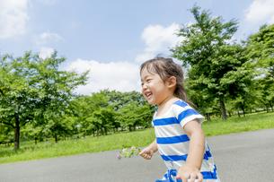 公園を花を持って走る女の子の素材 [FYI01075503]