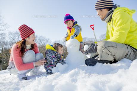 雪の公園で雪だるまを作って遊ぶ4人家族の素材 [FYI01075504]