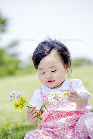 公園で笑いながら花を見る女の子の素材 [FYI01075505]