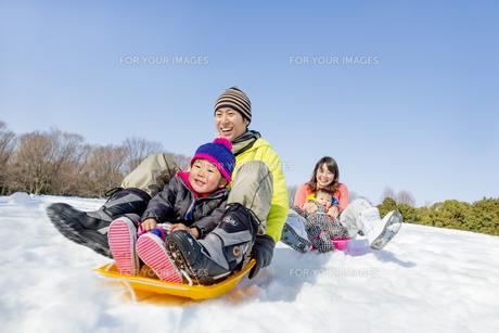 雪の公園でソリ遊びをする4人家族の素材 [FYI01075513]