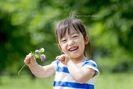 公園で、花を持って笑う女の子の素材 [FYI01075514]