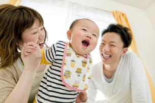 リビングで遊ぶ男の子と両親の素材 [FYI01075516]