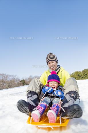 雪の公園でソリ遊びをする父と息子の素材 [FYI01075517]