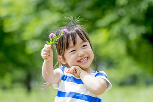 公園で、花を持って笑う女の子の素材 [FYI01075518]