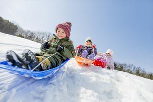 雪の公園でソリ遊びをする子供たちの素材 [FYI01075526]
