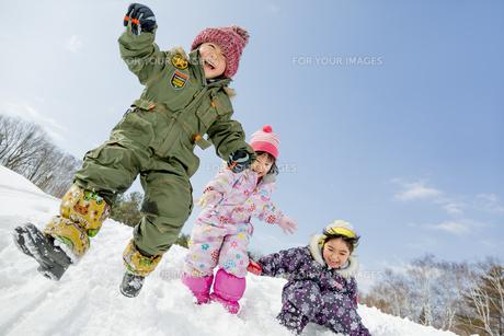雪の公園でジャンプする子供たちの素材 [FYI01075530]