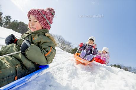 雪の公園でソリ遊びをする子供たちの素材 [FYI01075539]