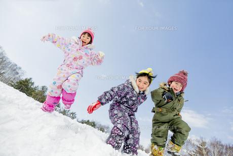 雪の公園でジャンプする子供たちの素材 [FYI01075540]