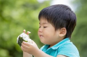 新緑の公園でおにぎりを食べる男の子の素材 [FYI01075545]
