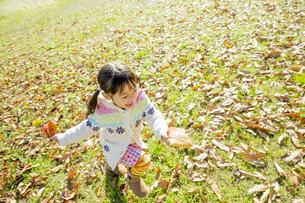 落葉の公園を葉っぱを持って走る女の子の素材 [FYI01075547]