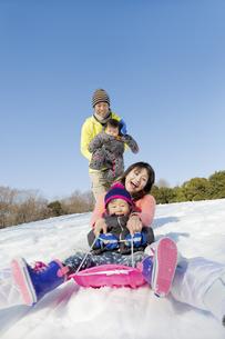 雪の公園でソリ遊びをする4人家族の素材 [FYI01075552]