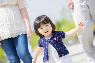公園を歩く女の子と両親の素材 [FYI01075561]