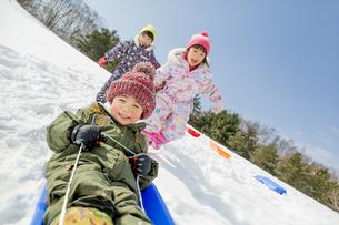 雪の公園でソリ遊びをする子供たちの素材 [FYI01075563]