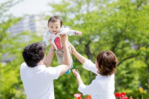 公園で息子を抱き上げる両親の素材 [FYI01075572]