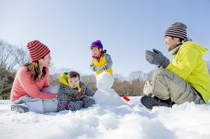 雪の公園で雪だるまを作って遊ぶ4人家族の素材 [FYI01075573]