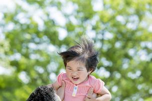 新緑の公園で父親に抱き上げられる娘の素材 [FYI01075577]