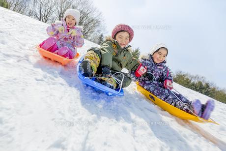 雪の公園でソリ遊びをする子供たちの素材 [FYI01075595]