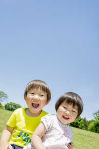 新緑の公園で遊ぶ兄と妹の素材 [FYI01075606]