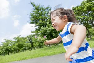 公園を花を持って走る女の子の素材 [FYI01075609]