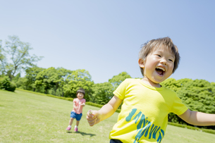 新緑の公園で遊ぶ兄と妹の素材 [FYI01075611]