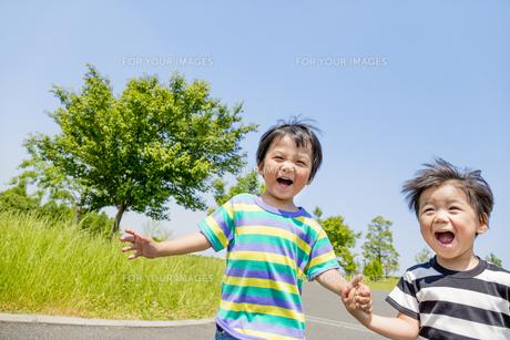 公園を手をつないで走る男の子たちの素材 [FYI01075613]