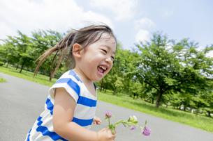 公園を花を持って走る女の子の素材 [FYI01075614]