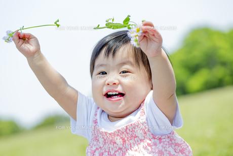 公園で笑いながら花を持つ女の子の素材 [FYI01075615]