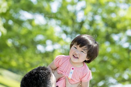 新緑の公園で父親に抱き上げられる娘の素材 [FYI01075625]